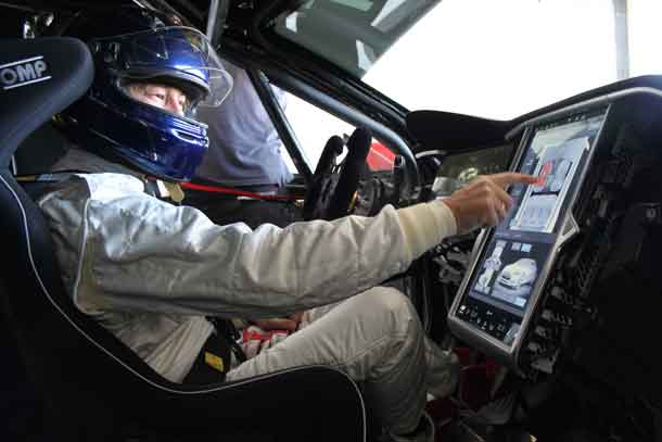 Heinz Harald Frentzen of Germany touching the screen e race version of a Tesla Model S P85+ after Frentzens race tests in Le Castellet, France, on 19-10-2016.