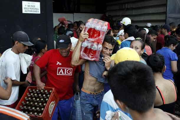 People carry goods taken from a food wholesaler after it was broken into, in La Fria, Venezuela December 17, 2016. REUTERS/Carlos Eduardo Ramirez