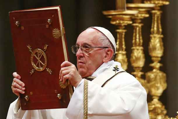 Pope Francis holds the book of the gospels as he leads the Christmas night Mass in Saint Peter's Basilica at the Vatican December 24, 2016. REUTERS/Tony Gentile