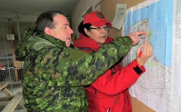 Warrant Officer Barry Borton, a 3 CRPG instructor, shows Corporal Paula Nakagee of Fort Albany how to use a map during a training exercise.