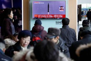 Passengers watch a TV screen broadcasting a news report on North Korea firing a ballistic missile into the sea off its east coast, at a railway station in Seoul, South Korea, February 12, 2017. REUTERS/Kim Hong-Ji