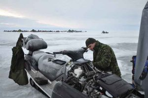 Thunder Bay Reservist Private Logan Dupuis of 38 Service Battalion works on repairing a snowmobile on Lake Winnipeg during Exercise ARCTIC BISON 2017. The exercise is 38 Canadian Brigade Group's Arctic Response Company Group's (ARCG) annual training opportunity that allows soldiers to train their non-tactical winter warfare skills. Photo Credit Cpl Natasha Tersigni, 28 CBG Public Affairs