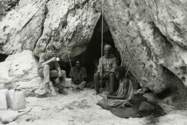 Rockshelter at Bathurst Head (Thartali) in eastern Cape York Peninsula, occupied by the expedition during field work. Pictured: Norman Tindale and local Aboriginal group. CREDIT Photo by Herbert Hale. February 1927. South Australian Museum Archives Norman Tindale Collection (AA 338/5/4/41)