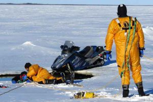 Canadian Rangers find and rescue a snowmobiler who has gone through the ice in a mock incident during a search and rescue exercise
