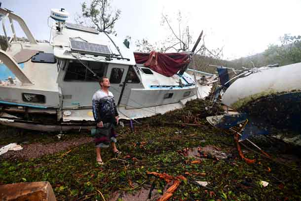Local resident Bradley Mitchell inspects the damage to a relative's boat after it smashed against the bank after Cyclone Debbie passed through the township of Airlie Beach, located south of the northern Australian city of Townsville. AAP/Dan Peled/via REUTERS
