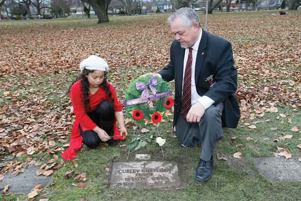 Rob Larman, a leg amputee, and Tiffany Ross, a left arm amputee and member of The War Amps Child Amputee (CHAMP) Program, lay a rose at the grave of Curley Christian, who lost all four limbs in the Vimy Ridge Battle, at Prospect Cemetery in Toronto, ON, Canada. (Photo by John E. Sokolowski/WarAmps)
