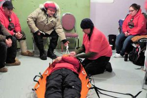 Sergeant Mary Miles shows Canadian Rangers how to use a new type of stretcher.