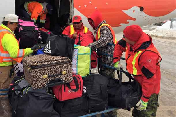 Canadian Rangers load evacuees' baggage onto plane.
