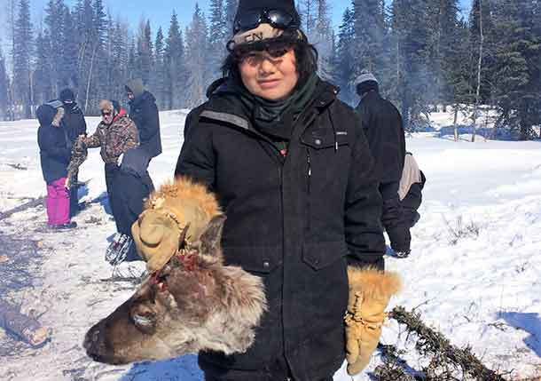 Junior Canadian Ranger Jay Cee Metatawabin with one of the caribou heads that was cooked and eaten. Credit: Warrant Officer Ron Wen