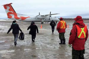 Canadian Rangers guide evacuees to plane at Kashechwan airport.