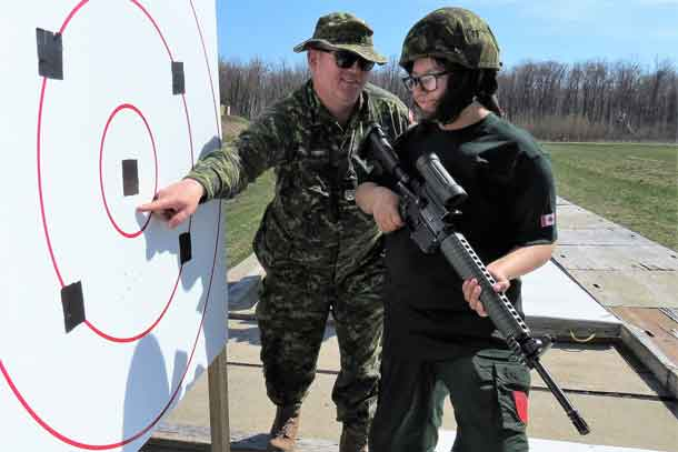 Master Warrant Officer James Currier, left, checks Junior Canadian Ranger Claudia Albany's shots on the target.