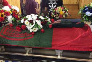A Junior Canadian Ranger flag and Junior Ranger cap and sweater drape the casket of Josiah Begg