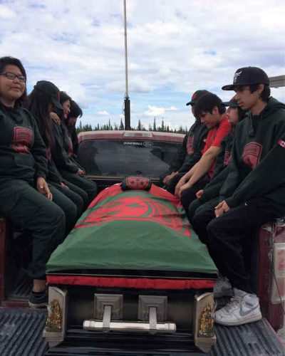 Junior Canadian Rangers, several crying, flank the casket as it is driven from the airport to the church.