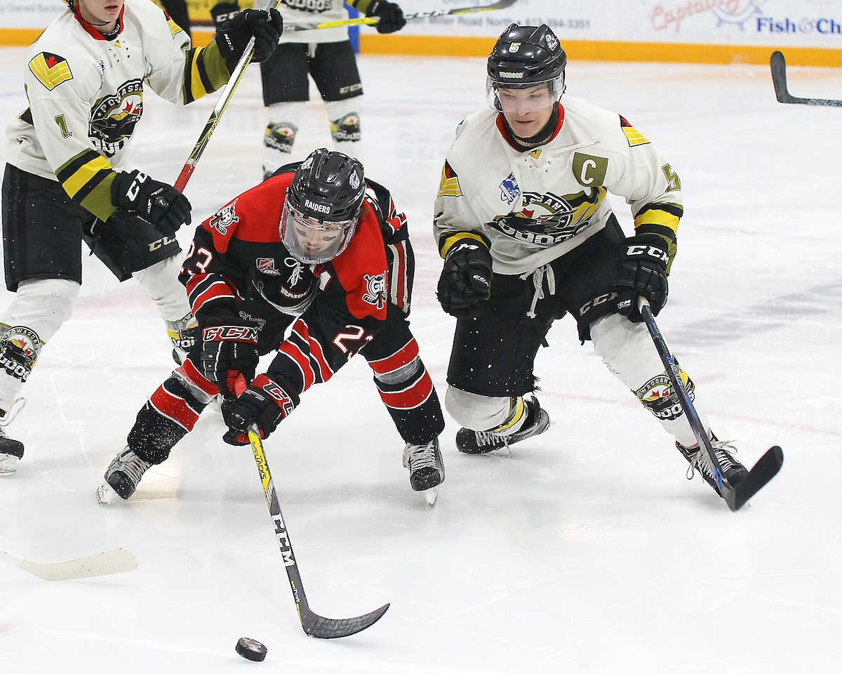 "TRENTON, ON - MAY 5, 2017: Canadian Junior Hockey League, Central Canadian Jr. ""A"" Championship. The Dudley Hewitt Cup Game 7 between Georgetown Raiders and the Powassan Voodoos. Jack Jacome #23 of the Georgetown Raiders reaches his stick out for the puck as Eric Nagy #5 of the Powassan Voodoos tries to hit him during the second period (Photo by Alex D'Addese / OJHL Images)"