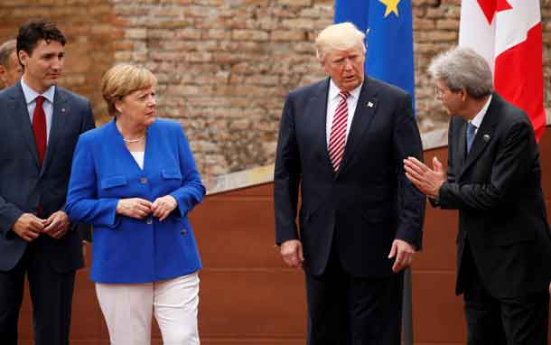 Italy's Prime Minister Paolo Gentolini (R) talks to Canada's Prime Minister Justin Trudeau (L), German Chancellor Angela Merkel and U.S. President Donald Trump while posing for a family photo at the start of G7 Summit at Greek Theatre in Taormina, Sicily, Italy, May 26, 2017. REUTERS/Jonathan Ernst
