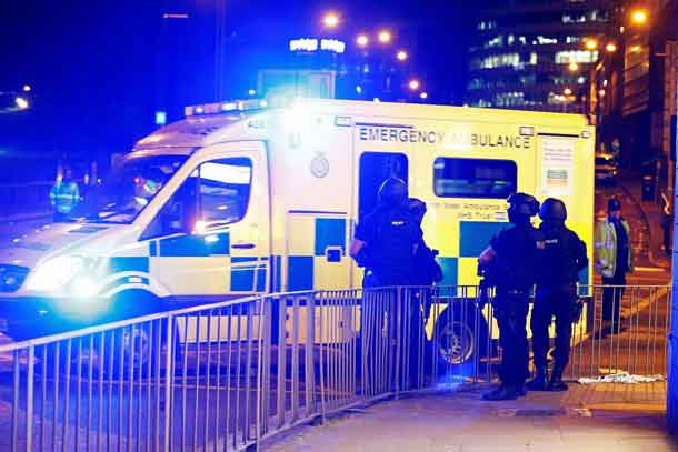Armed police officers stand near the Manchester Arena, where U.S. singer Ariana Grande had been performing, in Manchester, in northern England, Britain May 23, 2017. REUTERS/Andrew Yates