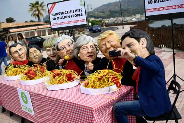 Protestors wearing masks depicting the leaders of the G7 countries pose for a selfie during a demonstration organised by Oxfam in Giardini Naxos, Sicily, Italy May 25, 2017. REUTERS/Dylan Martinez
