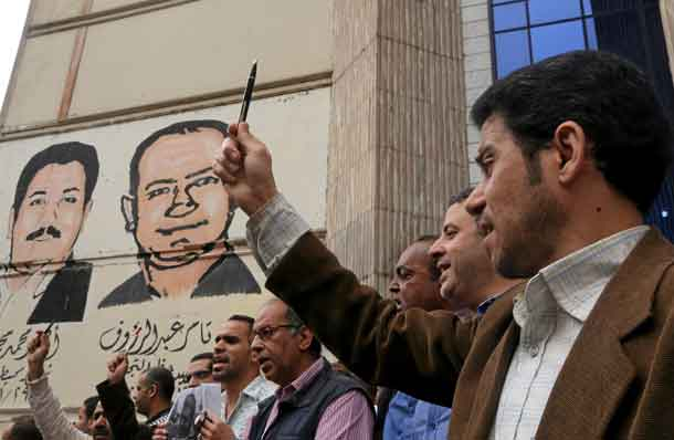 FILE PHOTO: A journalist holds up a pen during a protest against the detention of journalists, in front of the Press Syndicate in Cairo, Egypt April 26, 2016. REUTERS/Mohamed Abd El Ghany/File Photo