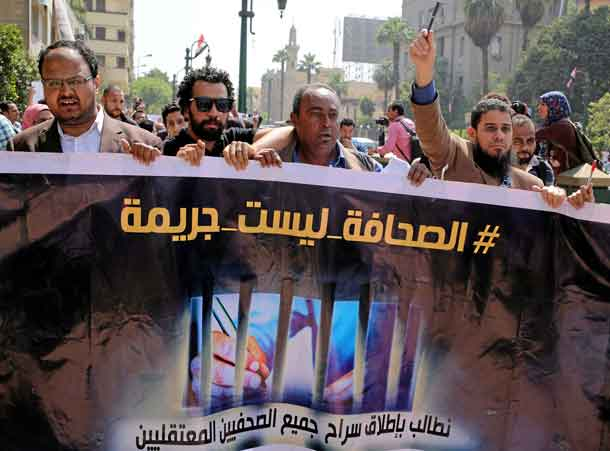 "FILE PHOTO: Egyptian journalists hold a banner outside the Egyptian Press Syndicate in downtown Cairo, Egypt April 28, 2016. The banner reads ""Press is not a crime."" REUTERS/Mohamed Abd El Ghany/File Photo"