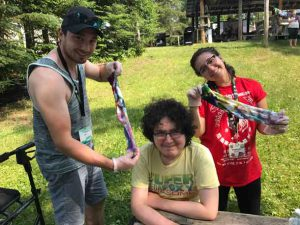 Companion Joe (left) with Camper Brendan and Companion Maddie holding up their tie-dye creation!