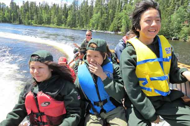 Junior Canadian Rangers react to a sharp turn in a power boat.
