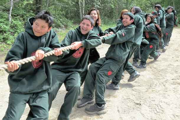 Junior Canadian Rangers winning a tug of war contest against soldiers.