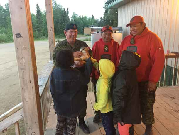 Warrant Officer Barry Borton, an army instructor, plays with a local puppy while talking to children in Wapekeka with Canadian Ranger Master Corporal Jacob McKay, centre, and Sergeant Spencer Anderson, right.  Credit: Lieutenant-Colonel Matthew Richardson, Canadian Rangers