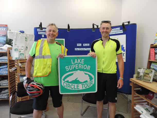 Greg Massey, 60, of Blaine, Minnesota, and son David, 29, of Minneapolis, biked around Lake Superior this summer to celebrate Greg's retirement. They began and ended the Circle Tour in Duluth, where they marked the accomplishment with a photo at the Lake Superior Circle Tour Headquarters, part of Lake Superior Magazine's offices at 310 E. Superior St. (Konnie LeMay / Lake Superior Magazine)