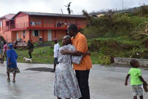 Barbuda has been hammered hard by hurricane winds. The Prime Minister seeks to console this woman.