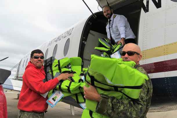 Ranger Redfern Wesley and Warrant Officer Carl Wolfe unload life jackets at Kashechewan airport.