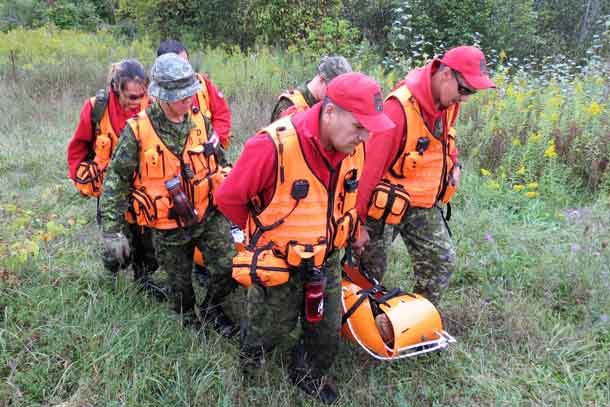 Canadian Rangers use a stretcher to carry a victim out of the bush during search and rescue training.