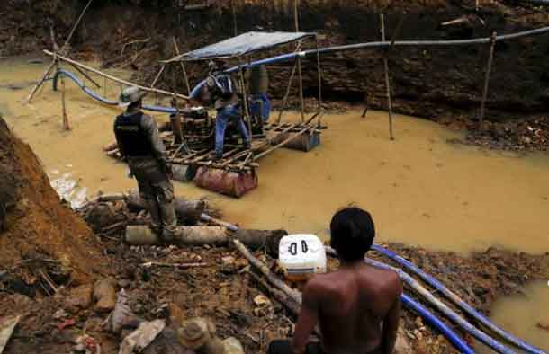 In this file photo, a Yanomami Indian (R) stands near an illegal gold mine during Brazil's environmental agency operation against illegal gold mining on indigenous land, in the heart of the Amazon Rainforest, in Roraima State, Brazil April 17, 2016. REUTERS/Bruno Kelly/File photo