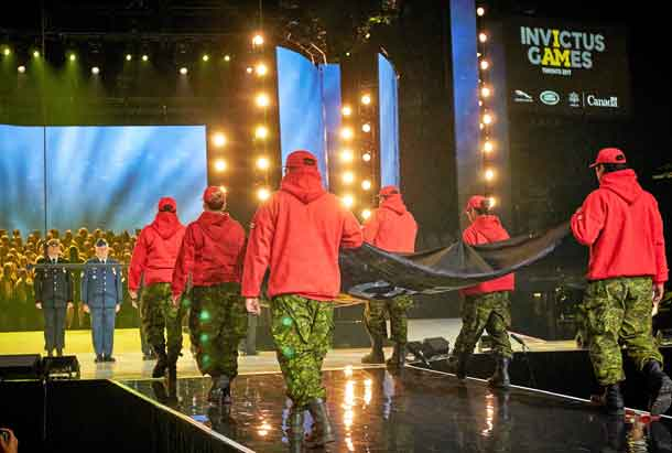 Canadian Rangers carry the Invictus Games flag across the arena floor to the stage.
