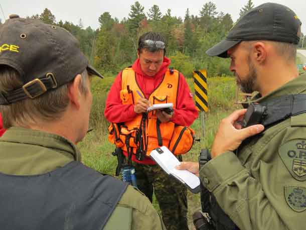 Master Corporal Shaun Kakegamic takes notes while two Ontario Provincial Police training officers tell him where to take a search part during search and rescue training. Credit: Sergeant Peter Moon, Canadian Rangers