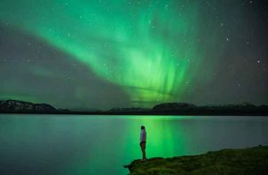 Man with Northern Lights reflection