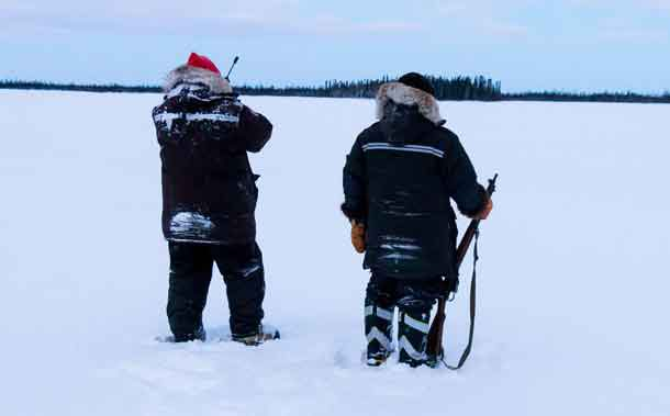 Sergeant Matthew Gull, left, and Corporal Maurice Mack check a lake for signs of the missing trapper. Photo by Jason Hunter