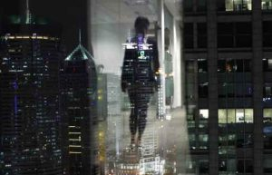A woman is reflected in a window of an office in the financial district of Pudong in Shanghai September 22, 2011. REUTERS/Carlos Barria