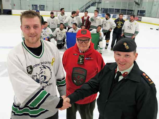 Master Corporal Adam Phelps of the Lorne Scots is congratulated on his team's win at hockey tournament supporting the Canadian Rangers by Colonel Dan Stepaniuk, right. John Newman, honorary lieutenant-colonel of the Rangers in Northern Ontario, is at centre. Credit Sergeant Peter Moon, Canadian Rangers