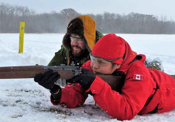 Ranger Jocelyn Yellowhead of Neskantaga shoots under the watchful eye of Sergeant Ben Kirke, an army instructor.