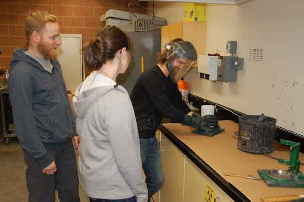 Civil Engineering Technology student Matt Watts (right) learns from technologist Tanya Belisle (middle) about how to cap concrete cylinders for testing as student Curtis Gural looks on