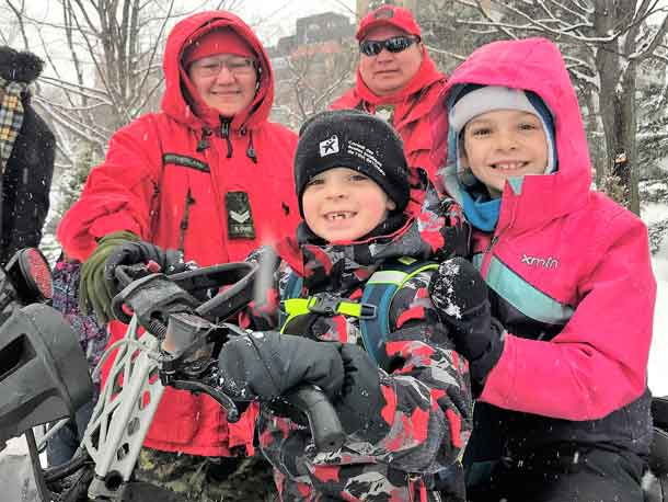 Corporal Jessie Sutherland, left rear, and Sergeant Matthew Gull, right rear, with two excited visitors sitting on a Canadian Ranger snowmobile. credit Captain Ted Dinning