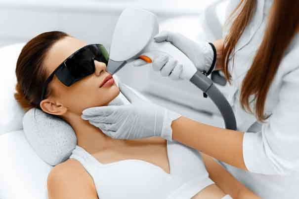 Facial Laser Hair Removal. Beautician Giving Laser Epilation Treatment To Young Woman's Face At Beauty Clinic. Image: Deposit Photos.com