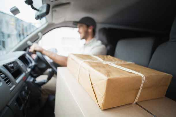 Delivery driver driving van with parcels on seat outside the warehouse - Image Depositphotos.com