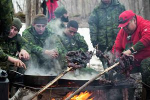 Sergeant Matthew Gull, right, shows soldiers from the Toronto Scottish Regiment how to cook geese over an outdoor fire.