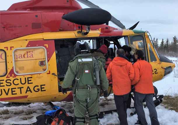 The injured snowmobiler is loaded on to an RCAF helicopter.
