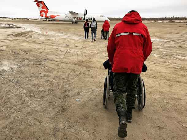 Canadian Rangers push elderly residents in wheelchairs to an evacuation plane in Kashechewan.