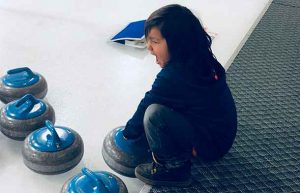 Curling fans of all ages are watching the action. Here Lamarith tests out how heavy a curling stone really is. - James Murray photo.