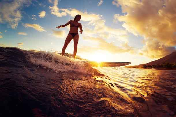 Surfing at Sunset. Beautiful Young Woman Riding Wave at Sunset. Image by Depositphotos.com