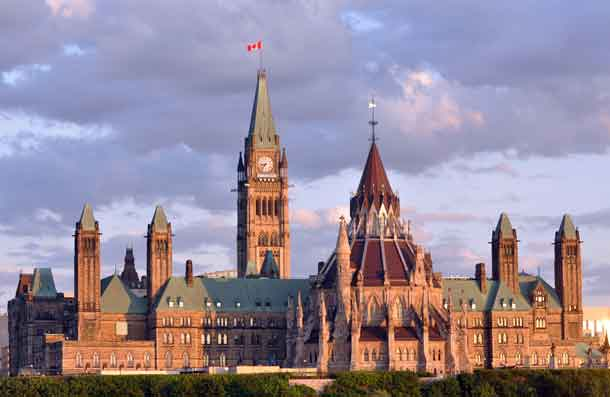 The back of the Parliament Building in Ottawa taken before sunset. The Peace Tower is in the background and the Library is in the foreground.