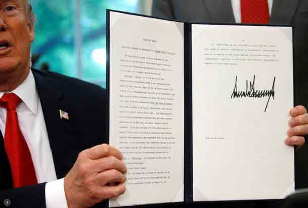 President Donald Trump displays an executive order on immigration policy after signing it in the Oval Office at the White House in Washington, U.S., June 20, 2018. REUTERS/Leah Millis